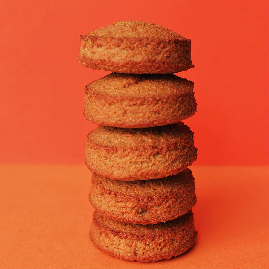 5 Keto pumpkin spice cookies stacked on an orange background