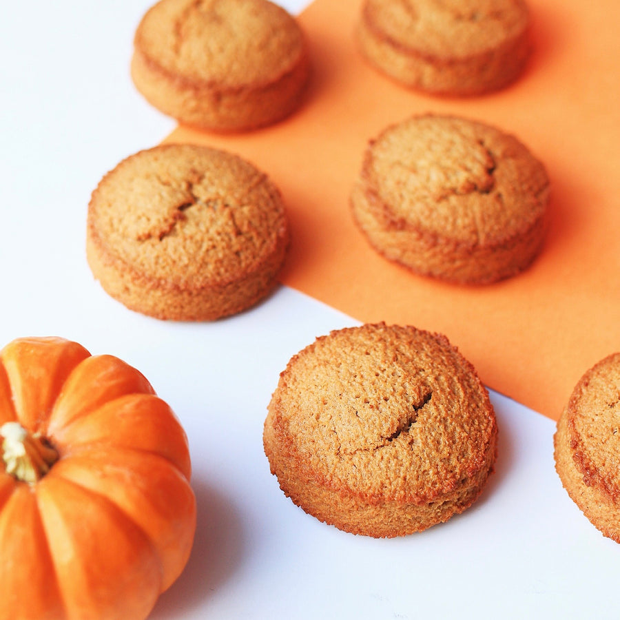 Keto pumpkin spice cookies on an orange background with a pumpkin on the left hand side.