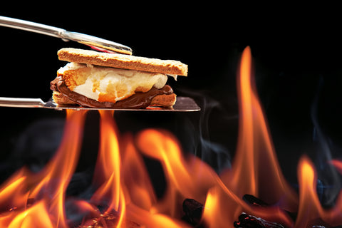 Hot, Smoldering, campfire burning with metal tongs holding a fresh Smore with gram crackers, toasted marsh-mellow and melted milk chocolate.