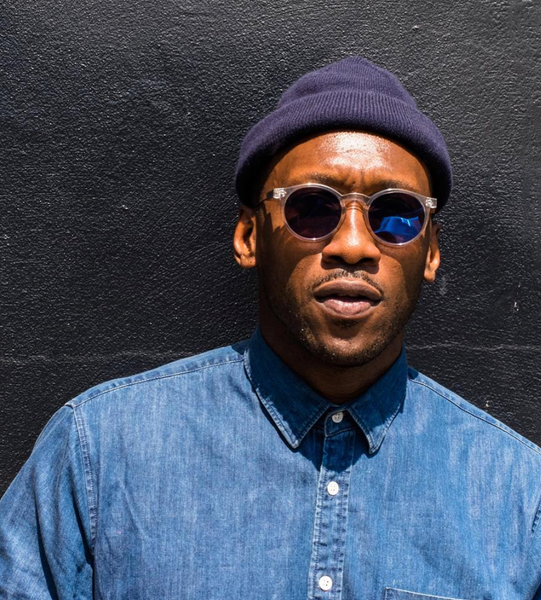 Mahershala Ali wearing a beanie and shades for a photo.