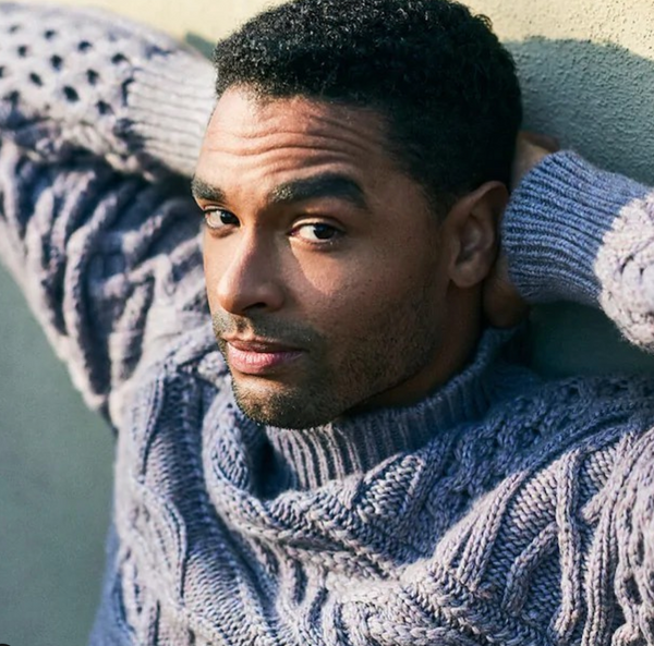 Rege-Jean Page posing with his hands behind his back while wearing a turtleneck sweater.