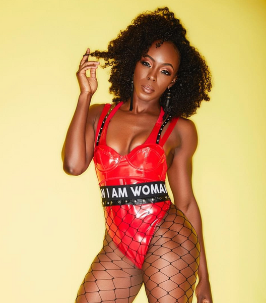 Black woman in red leather bodysuit and fishnet stockings.