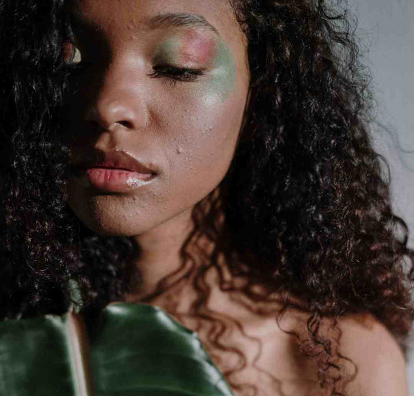 Black girl with curly hair in natural make-up.