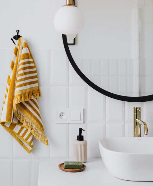 Bathroom sink with a round mirror and yellow towel.