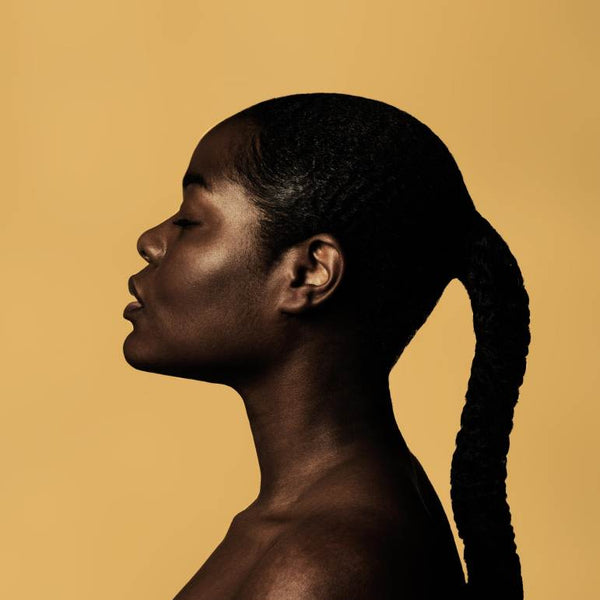 Girl in a braided ponytail posing sideways against a yellow background.