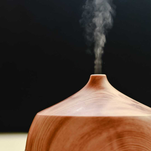 Essential oil diffuser with smoke steaming on top.