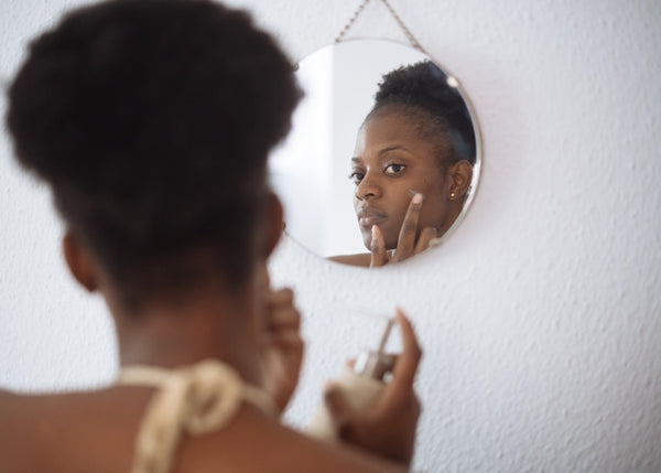 Black woman applying skin care and looking in mirror.