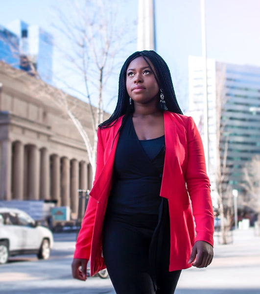 Black girl boss in a red jacket on the street.