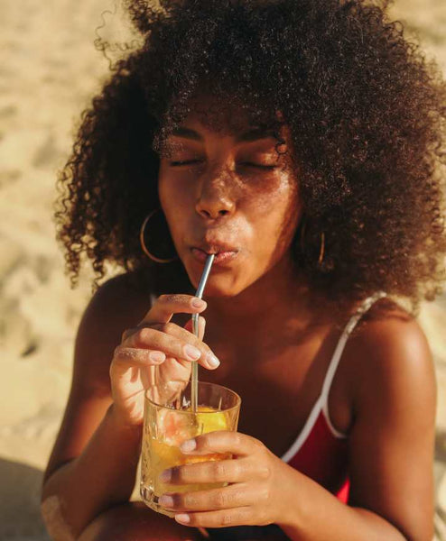 Girl sipping a refreshing drink while at the beach.