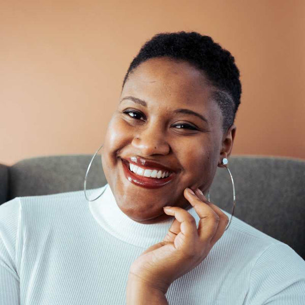 Black girl smiling with her hand resting on her face.