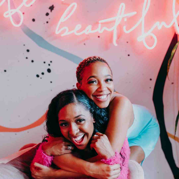 Two black women smiling and hugging each other.