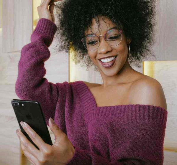 Black woman fixing her hair while looking at her cellphone.