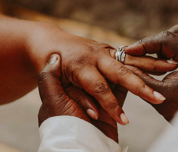Hands of a man and woman exchanging wedding rings.