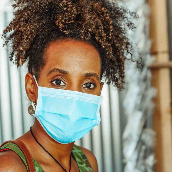 Black woman wearing a surgical face mask.