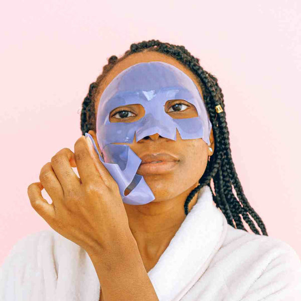 Black woman in a bathrobe with a facial mask on.