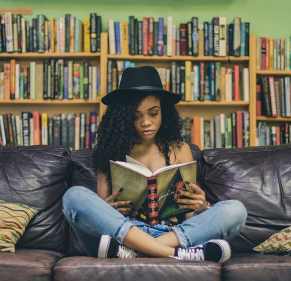 Girl reading a book while sitting on a sofa.