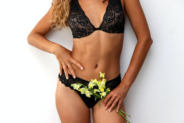 Black woman showing her abs while wearing lace lingerie.