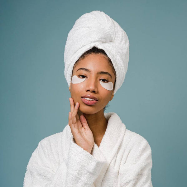Girl in a bathrobe with towel in her hair and under-eye mask.