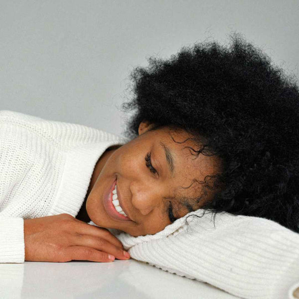 Black girl resting on her arm with her eyes closed.