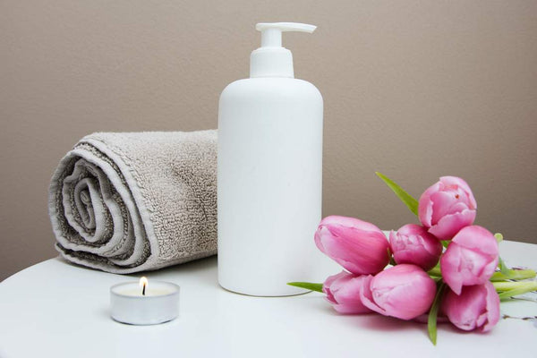 Towel, lotion and pink roses on a table.