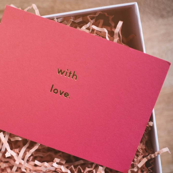 With love pink card on a gift box.