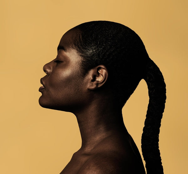 Black woman in braided ponytail with yellow background.