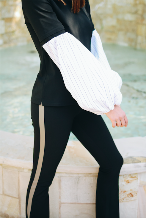 woman wearing black pants with gold stripe