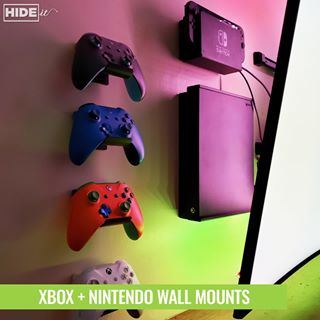 Xbox console and controllers plus Nintendo Switch wall mounted using HIDEit Mounts behind wall-mounted TV