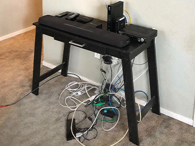 Close up of table with devices and messy cords on floor