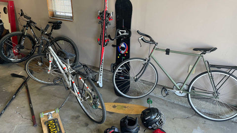Garage cleanup with bikes, skis, a snowboard, helmets, and a skateboard laying on the ground.