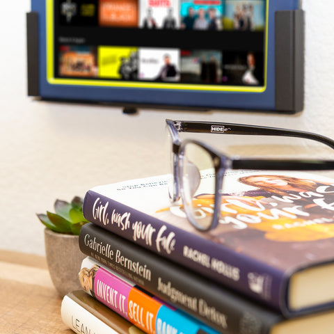 HIDEit blue light gaming glasses sitting on books with HIDEit tablet mount wall mounted