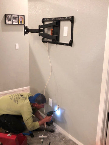 TV wall mount on wall without TV, man drilling hole to move power outlet
