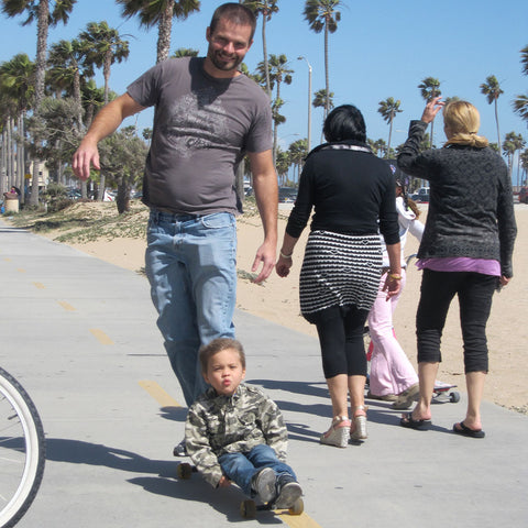 Dad riding a longboard with a child in Newport Beach