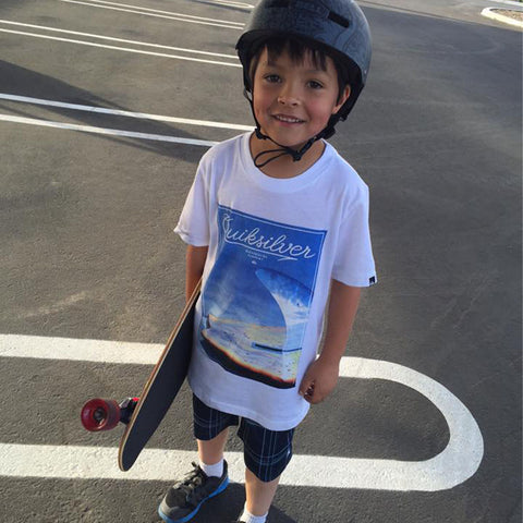 Young boy with complete skateboard and helmet