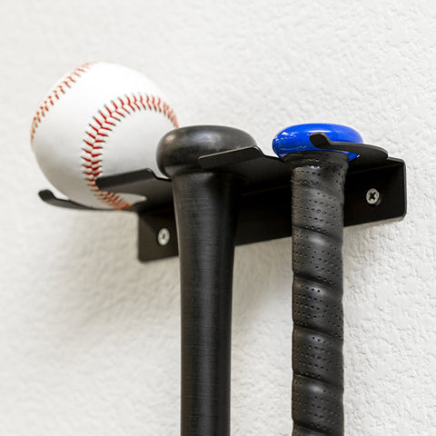 HIDEit Triple Bat Mount hanging in a room with two bats and a baseball.