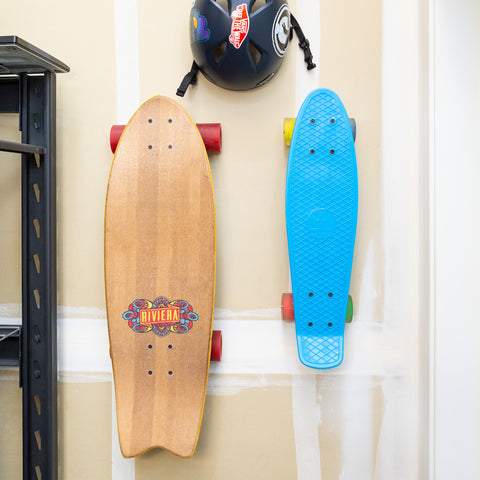 Riviera skateboard and penny board mounted in garage with HIDEit Vertical Skateboard Mounts.