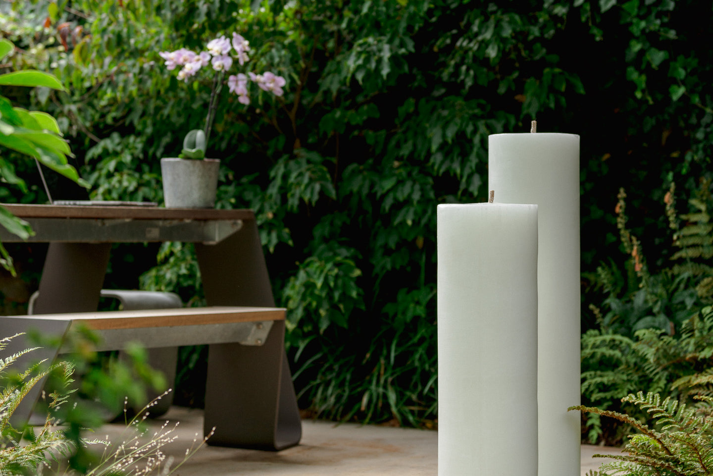 Two standing MAJO RUMI 1 metre tall, white outdoor garden pillar candles, not lit, in garden setting with garden bench