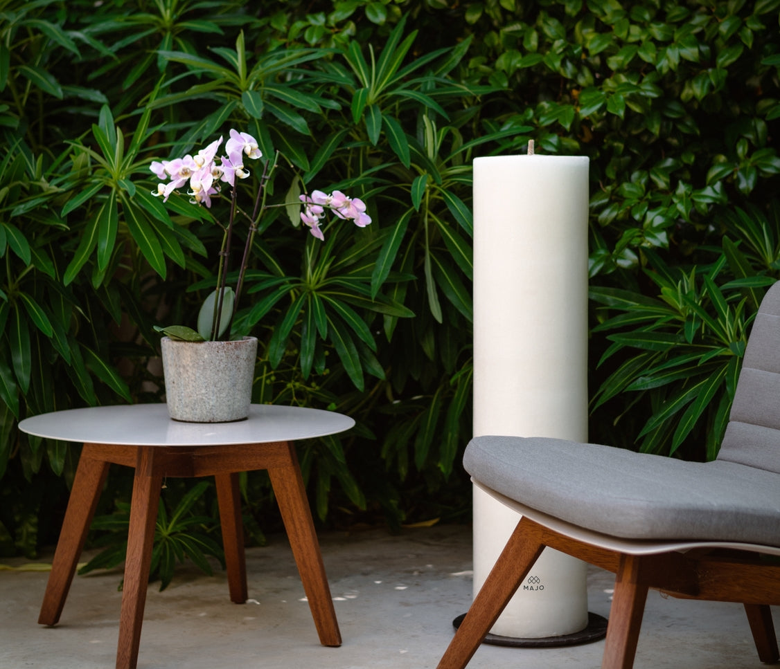 MAJO RUMI 1 metre tall white outdoor pillar candle with MAJO logo, not lit, in garden setting with garden furniture, chair and table