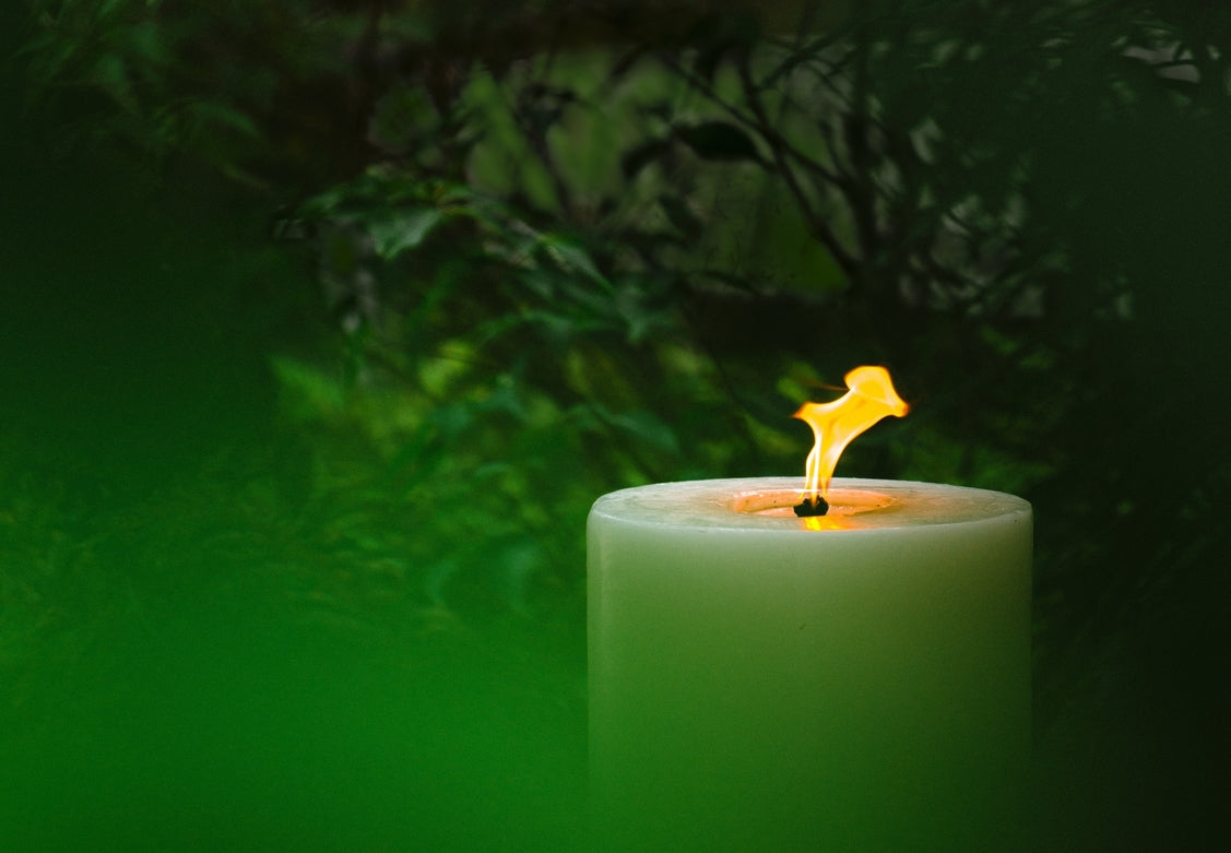 MAJO LUSO 60 cm white outdoor garden pillar candle lit with large flame shown glowing through the green foliage of the garden