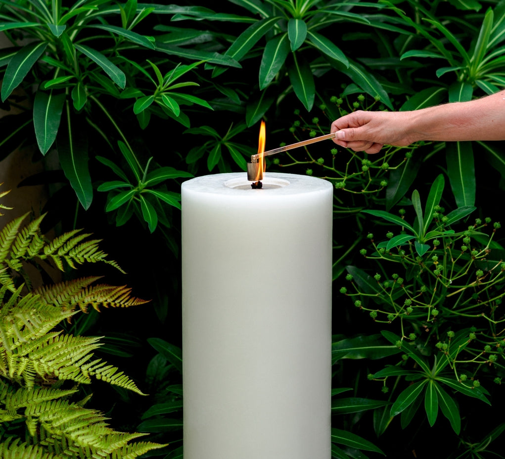 MAJO LUSO 80 cm white outdoor garden pillar candle lit with large flame and hand with candle snuffer extinguishing flame, in a garden setting