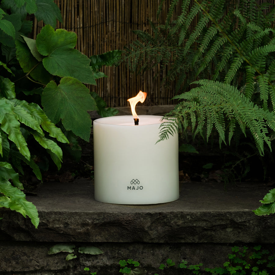 MAJO 20 cm large candle for outside in the garden. MAJO Candle lit with large flame on a step with ferns and foliage.