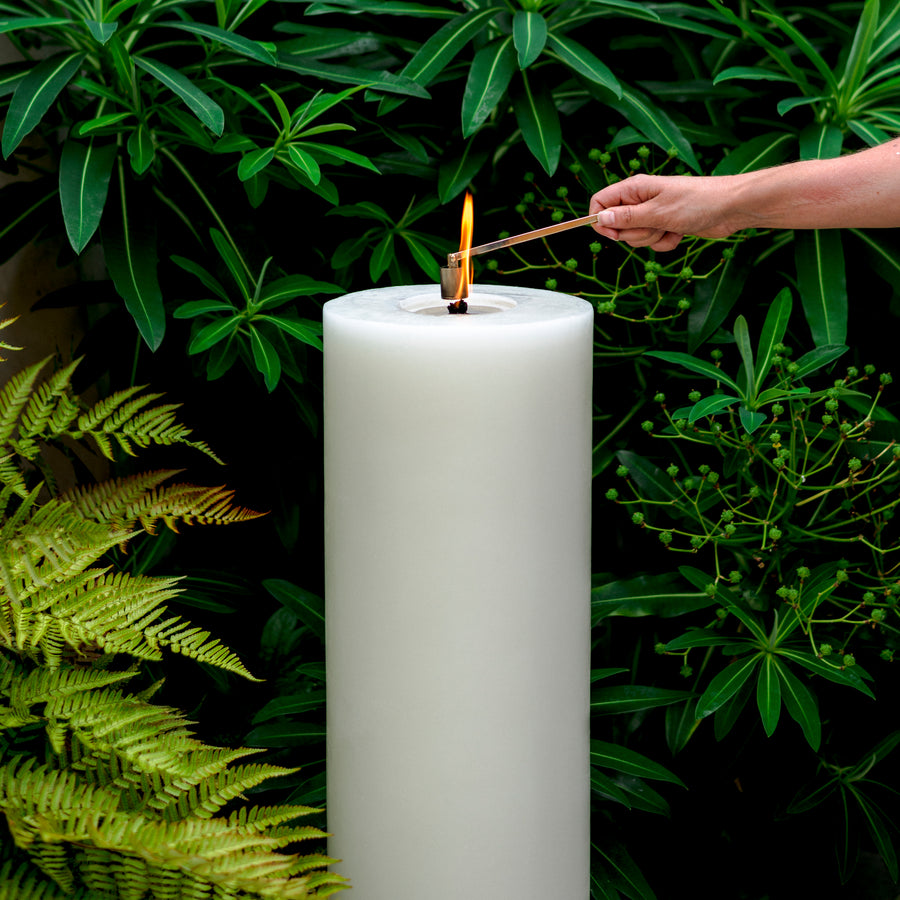 MAJO outdoor garden candle 60cm tall with hand holding snuffer over flame