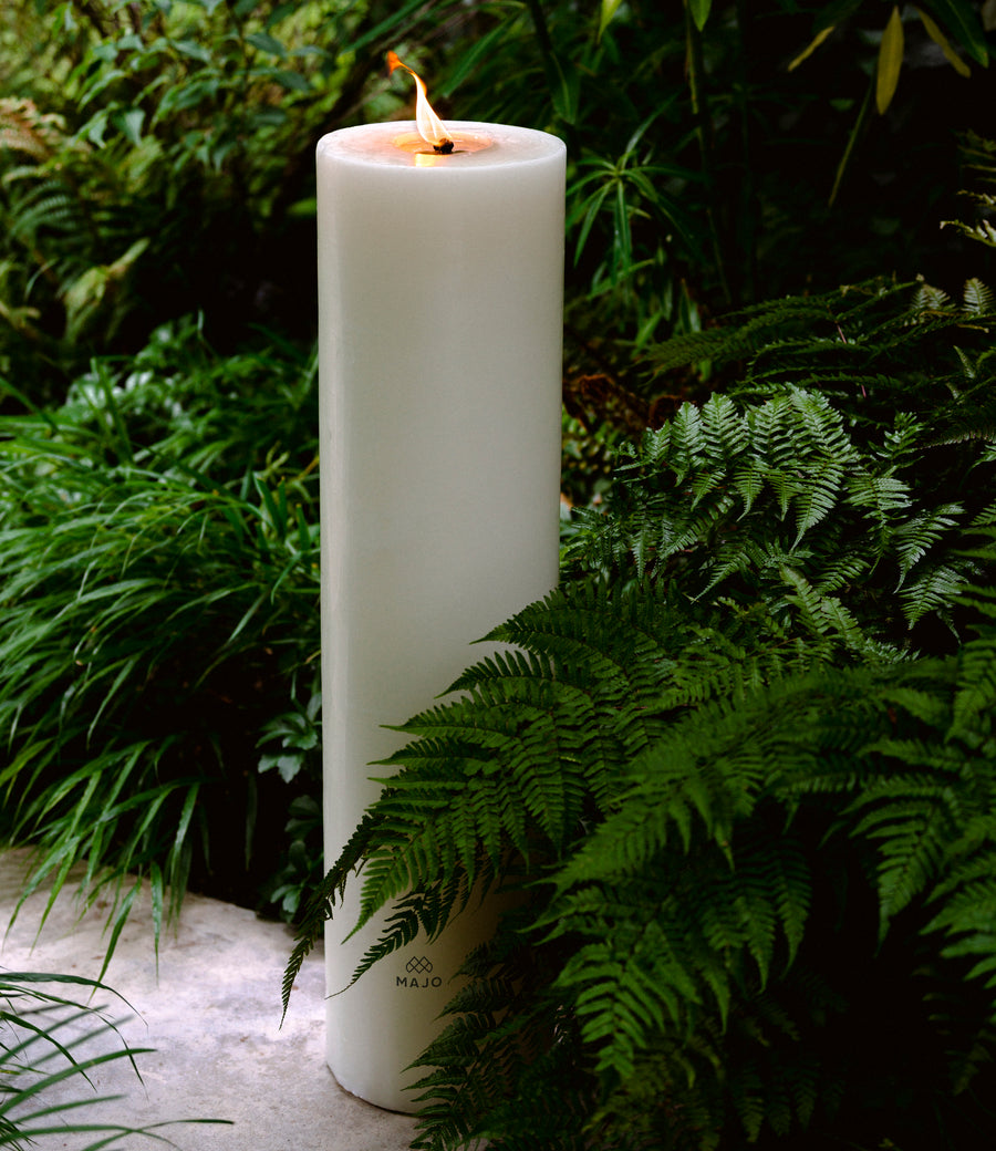 MAJO large outdoor garden candle 80cm tall lit on concrete path with ferns and grass.