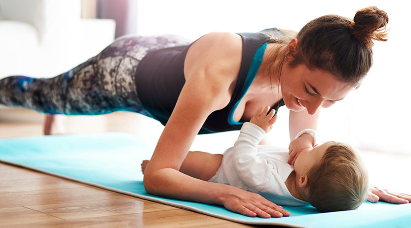 Lady doing yoga with her baby