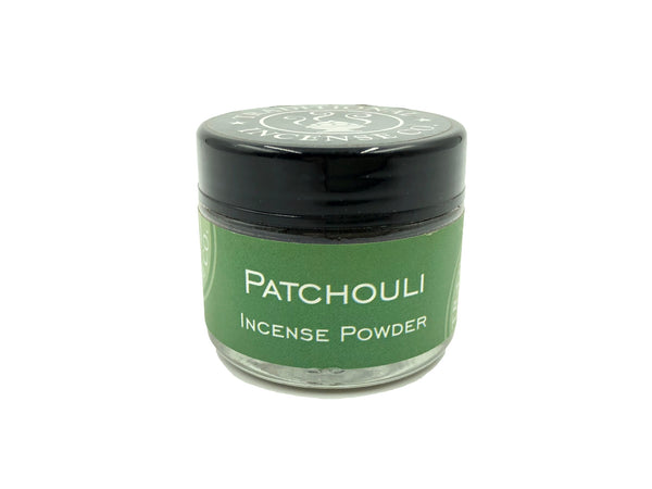 Small round, glass container holding patchouli incense powder