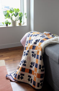 The Weekend Quilter Plaidful Modern Quilt Pattern for confident beginners in throw styled on couch