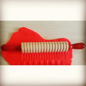 textured rolling pin with red handles