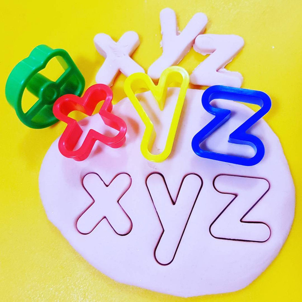 x y z stamped into and cut out from playdough using alphabet cutters.