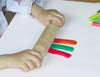 child rolling playdough with wooden rolling pin