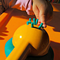 child playing with playdough extruded from lemon juicer